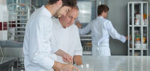 Apprenti cuisinier écoutant son maître d'apprentissage